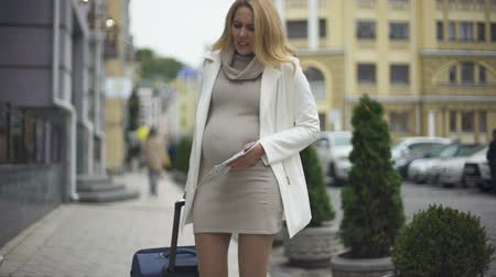 belly : Travelling pregnant lady with suitcase and map feeling belly pain on city street