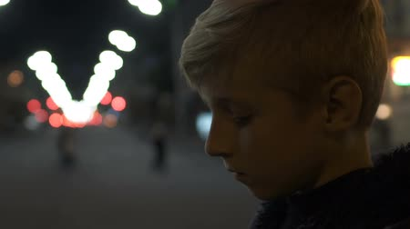 ártatlanság : Sad boy standing alone on street at holiday eve bullying problem lack of friends Stock mozgókép