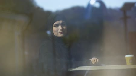 direitos : Beautiful thoughtful Muslim lady sitting in cafe wearing hijab waiting for order