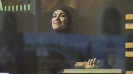 prejudice : Young attractive Muslim female in cafe enjoying sunshine.
