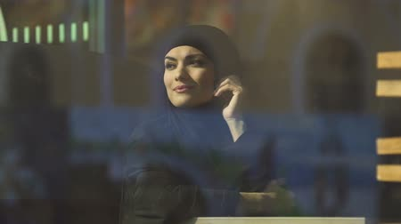 prejudice : Attractive Muslim lady in hijab sitting in cafe, looking in window, dreaming