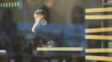 prejudice : Attractive Muslim lady drinking coffee in cafe, looking in window, dreaming