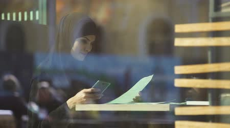 direitos : Beautiful Muslim lady freelancer working in cafe, chatting with partner on phone