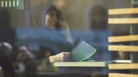 prejudice : Young attractive Muslim student in cafe preparing for exams, calling friend