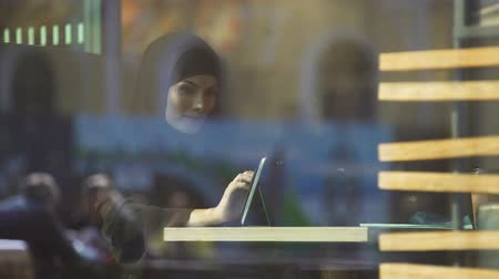 prejudice : Beautiful Muslim female sitting in cafe, using shopping app on tablet, banking Stock Footage