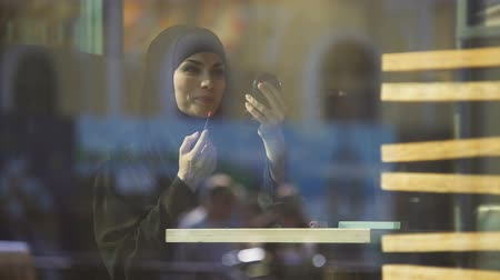 prejudice : Attractive self-confident Muslim lady applying lipstick sitting in cafe, smiling