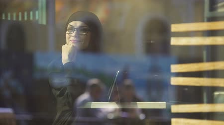 prejudice : Happy peaceful Muslim lady in cafe sitting near window, looking outside, freedom Stock Footage