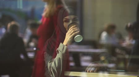 prejudice : Free Muslim lady drinking coffee in cafe, thinking about opportunities, smiling