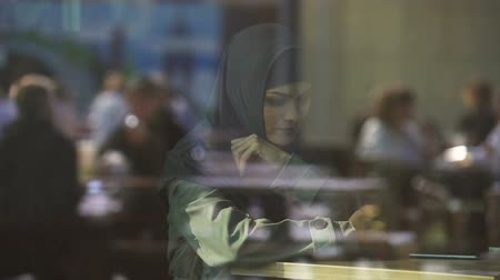 szerény : Depressed woman in traditional Muslim hijab in cafe, hardship in new country Stock mozgókép