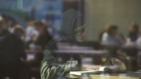 self motivated : Young Arabic lady reading book in cafe, student preparing for exams, literature