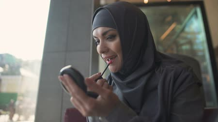 szerény : Attractive lady in traditional hijab applying lip balm in cafe smiling in mirror