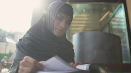 direitos : Motivated Muslim female student reading book in cafe modern education literature