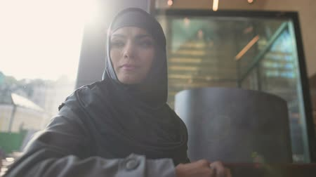 condemnation : Depressed Arabic female in cafe thinking, uncertain of decision, insecurities. Stock Footage