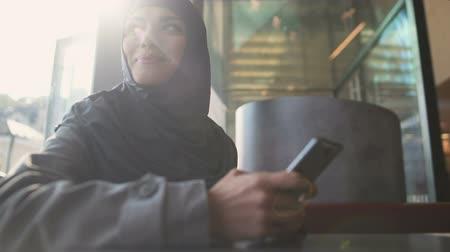 direitos : Inspired Muslim lady reading message on phone, getting new job, employment