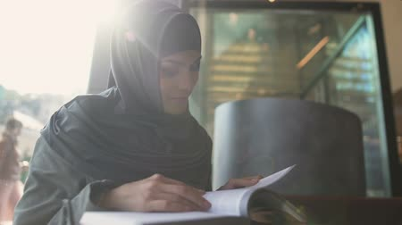self motivated : Self-confident Arabic lady reading book in cafe, education and self-development