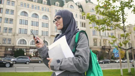 szerény : Inspired confident Muslim female student chatting on phone, standing on street Stock mozgókép