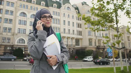 szerény : Self-confident smiling Muslim female student talking on phone standing on street Stock mozgókép