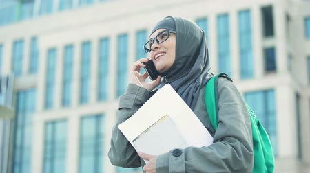 bescheiden : Cheerful Arabic female student talking on phone standing on university campus
