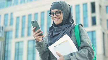 szerény : Happy Muslim woman student chatting on phone outdoors on university campus