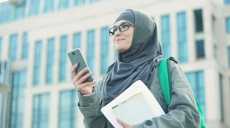 direitos : Inspired Muslim lady receiving message on phone, getting new job, employment