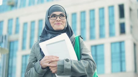 self motivated : Motivated young Muslim student thinking about prospects outdoors, university Stock Footage