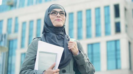 szerény : Inspired young female student wearing hijab smiling, standing outdoors on campus Stock mozgókép