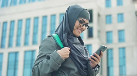 self motivated : Cheerful Muslim student chatting on phone, writing email, free to communicate