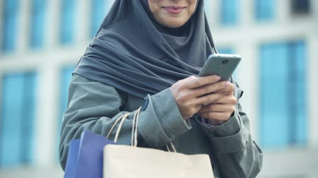 véu : Smiling Arabic lady outdoors chatting on phone after successful shopping fashion