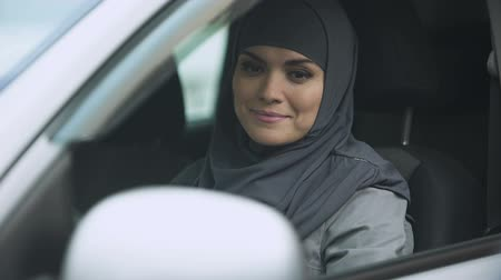 self driving : Young Muslim lady preparing to drive, business lady going to meeting, license Stock Footage