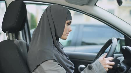 self driving : Muslim lady sitting in car starting engine and looking in mirror driving license Stock Footage