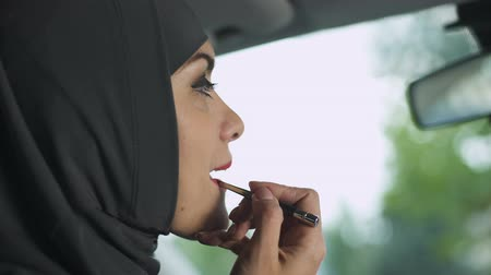self driving : Seductive Muslim lady applying red lipstick in automobile, feminism, coquette