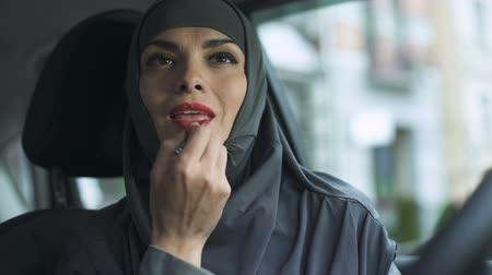engedély : Attractive sexy lady in hijab applying red lipstick in automobile feminism. Stock mozgókép