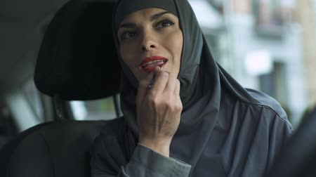 engedély : Self-confident Arabic lady applying red lipstick in auto, flirting winking