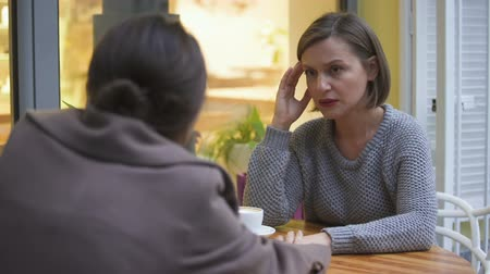 hot news : Lady comforting upset female friend in cafe, sisters having trustful relations Stock Footage