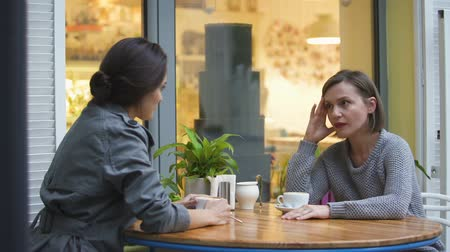 hot news : Two friends sitting in cafe, discussing family problems, lady comforting sister