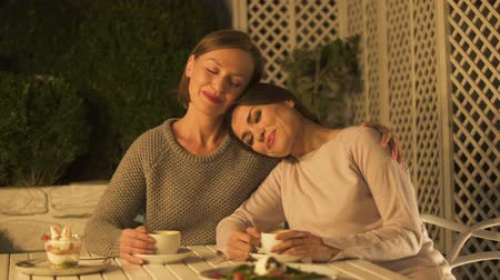 sisters : Happy lady hugging best friend, sitting on cafe terrace, having pleasant talk