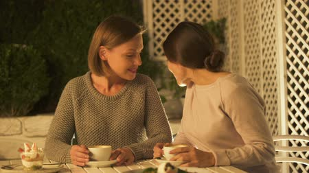latest : Funny female friends discussing latest gossips, drinking coffee and laughing