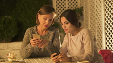 booking : Two ladies discussing travel destination, using mobile app for booking hotel Stock Footage