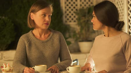 jealous : Two female friends arguing and shouting, sitting in cafe, misunderstanding Stock Footage