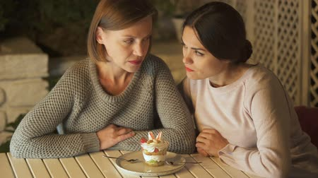 látszó el : Female friends deciding to avoid eating sugary desserts, moving plate away