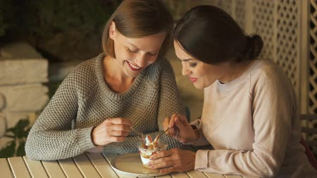 seduce : Two happy sisters eating sweet creamy dessert, having pleasure time together