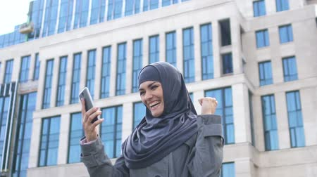 extremely : Excited Muslim girl reads message on phone about job hiring or entering college Stock Footage