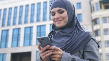 восхищенный : Pretty Muslim woman using smartphone, smiling after read message with good news