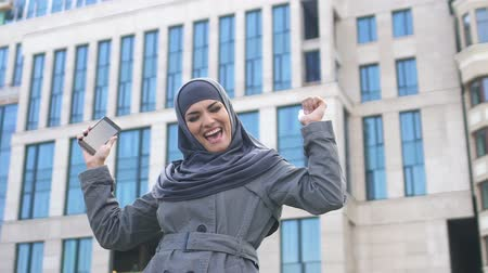 extremely : Muslim girl showing Yes gesture after read good news on phone, successful career Stock Footage