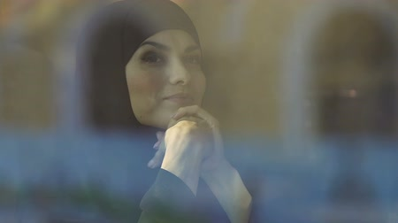 delighted : Happy Muslim girl looking through window, feels free and successful, closeup