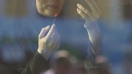 запрещенный : Muslim girl applying lipstick in public, ban for islamic women on cosmetics