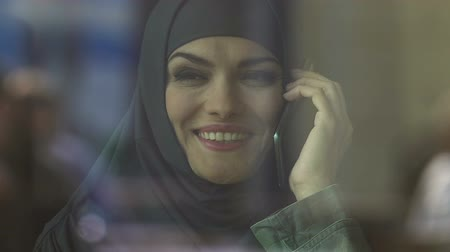 příznivý : Happy Muslim woman talking on phone, favorable tariffs of mobile operator