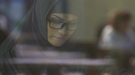direitos : Smart Muslim woman in eyeglasses reading book, preparing for entrance exams