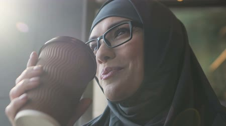educado : Happy Muslim woman drinking coffee, teacher relaxing after classes, closeup