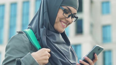 обмен сообщениями : Happy Arab girl using smartphone, chatting with friends after classes in college